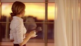 Η νέα γυναίκα ομορφιάς ανοίγει τις κουρτίνες στο μεγάλο παράθυρο και κοιτάζει από το απόθεμα βίντεο
