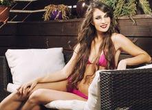Η νέα γυναίκα ομορφιάς μετά από τη SPA στο μπικίνι και η τήβεννος στο ξενοδοχείο προσφεύγουν, στο πεζούλι απολαμβάνοντας το θερμό στοκ εικόνες με δικαίωμα ελεύθερης χρήσης