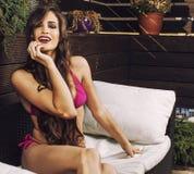 Η νέα γυναίκα ομορφιάς μετά από τη SPA στο μπικίνι και η τήβεννος στο ξενοδοχείο προσφεύγουν, στο πεζούλι απολαμβάνοντας το θερμό στοκ εικόνες