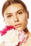 Η νέα γυναίκα ομορφιάς με μαλακό τρυφερό ευγενή κινηματογραφήσεων σε πρώτο πλάνο λουλουδιών peony ρόδινο makeup κοιτάζει Στοκ Εικόνες