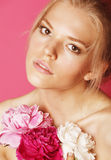 Η νέα γυναίκα ομορφιάς με μαλακό τρυφερό ευγενή κινηματογραφήσεων σε πρώτο πλάνο λουλουδιών peony ρόδινο makeup κοιτάζει Στοκ Εικόνα