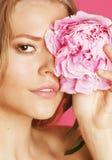 Η νέα γυναίκα ομορφιάς με μαλακό τρυφερό ευγενή κινηματογραφήσεων σε πρώτο πλάνο λουλουδιών peony ρόδινο makeup κοιτάζει Στοκ Φωτογραφία
