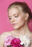 Η νέα γυναίκα ομορφιάς με μαλακό τρυφερό ευγενή κινηματογραφήσεων σε πρώτο πλάνο λουλουδιών peony ρόδινο makeup κοιτάζει Στοκ Φωτογραφίες