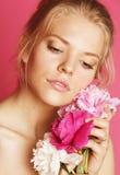 Η νέα γυναίκα ομορφιάς με μαλακό τρυφερό ευγενή κινηματογραφήσεων σε πρώτο πλάνο λουλουδιών peony ρόδινο makeup κοιτάζει Στοκ φωτογραφία με δικαίωμα ελεύθερης χρήσης
