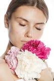 Η νέα γυναίκα ομορφιάς με μαλακό τρυφερό ευγενή κινηματογραφήσεων σε πρώτο πλάνο λουλουδιών peony ρόδινο makeup κοιτάζει Στοκ εικόνες με δικαίωμα ελεύθερης χρήσης