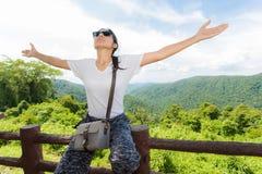 Η νέα γυναίκα οπλίζει αυξημένος απολαμβάνοντας το καθαρό αέρα στοκ εικόνα