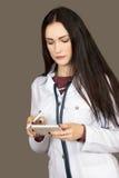 Η νέα γυναίκα ο γιατρός σε έναν άσπρο επίδεσμο ντύνει Στοκ Εικόνες