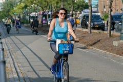 Η νέα γυναίκα οδηγά ένα Citibike Στοκ Εικόνα