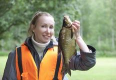 Η νέα γυναίκα ο ψαράς με επίασε bream στοκ εικόνες
