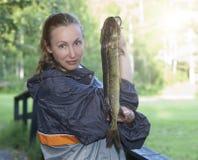 Η νέα γυναίκα ο ψαράς με τους πιασμένους λούτσους στοκ εικόνα