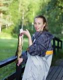 Η νέα γυναίκα ο ψαράς με τους πιασμένους λούτσους στοκ φωτογραφία