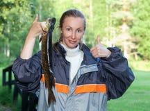 Η νέα γυναίκα ο ψαράς με τους πιασμένους λούτσους στοκ εικόνες με δικαίωμα ελεύθερης χρήσης