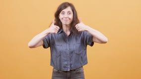 Η νέα γυναίκα πέρα από το κίτρινο υπόβαθρο που παρουσιάζει αντίχειρες υπογράφει επάνω απόθεμα βίντεο