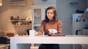 Η νέα γυναίκα πίνει από ένα φλυτζάνι με το συνθετικό χέρι της φιλμ μικρού μήκους
