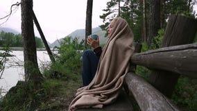 Η νέα γυναίκα πίνει τον καυτό καφέ ή το τσάι κοντά στον ποταμό βουνών Ήρεμος και άνετος χρόνος στο θέρετρο βουνών απόθεμα βίντεο