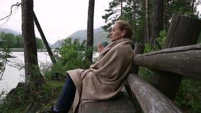 Η νέα γυναίκα πίνει τον καυτό καφέ ή το τσάι κοντά στον ποταμό βουνών Ήρεμος και άνετος χρόνος στο θέρετρο βουνών φιλμ μικρού μήκους