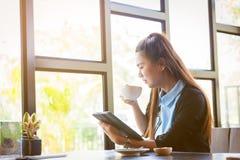 Η νέα γυναίκα πίνει τον καφέ με τη χρησιμοποίηση της ταμπλέτας στη καφετερία Στοκ εικόνες με δικαίωμα ελεύθερης χρήσης