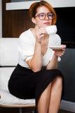 Η νέα γυναίκα πίνει τον καφέ στο γραφείο Στοκ Φωτογραφίες