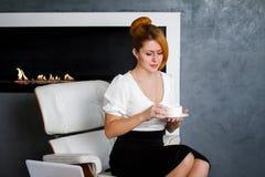 Η νέα γυναίκα πίνει τον καφέ στο γραφείο Στοκ Εικόνες