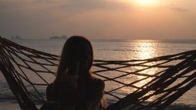 Η νέα γυναίκα πίνει το κοκτέιλ που ταλαντεύεται στην αιώρα στο ηλιοβασίλεμα απόθεμα βίντεο
