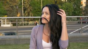 Η νέα γυναίκα παίζει με την τρίχα της που απεικονίζει ένα mustache Καλό κορίτσι που έχει τη διασκέδαση στην οδό Αλυσίδα με έναν σ απόθεμα βίντεο