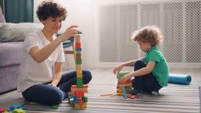 Η νέα γυναίκα παίζει με το παιδί με τους φραγμούς κατασκευής, το αγόρι έχει τη διασκέδαση φιλμ μικρού μήκους