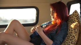 Η νέα γυναίκα παίζει το ξάπλωμα ukulele στον καναπέ στο ρυμουλκό φιλμ μικρού μήκους