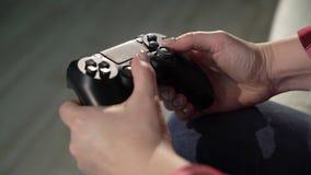 Η νέα γυναίκα παίζει το τηλεοπτικό παιχνίδι χρησιμοποιώντας ένα gamepad closeup απόθεμα βίντεο