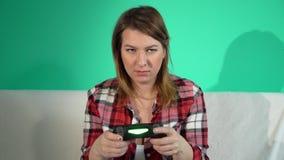 Η νέα γυναίκα παίζει το τηλεοπτικό παιχνίδι χρησιμοποιώντας ένα gamepad closeup φιλμ μικρού μήκους