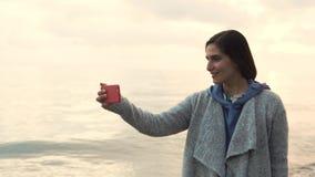 Η νέα γυναίκα παίρνει μια φωτογραφία στο τηλέφωνο της θάλασσας μένοντας κοντά στο νερό φιλμ μικρού μήκους