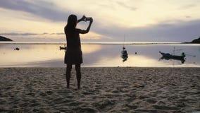 Η νέα γυναίκα παίρνει τη φωτογραφία του καταπληκτικού ηλιοβασιλέματος με το έξυπνο τηλέφωνο στην τροπική παραλία 3840x2160 απόθεμα βίντεο