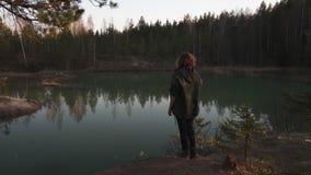 Η νέα γυναίκα παίρνει τη φωτογραφία χρησιμοποιώντας το τηλέφωνό της app μιας τυρκουάζ λίμνης χρώματος στα κράτη της Βαλτικής στη  απόθεμα βίντεο