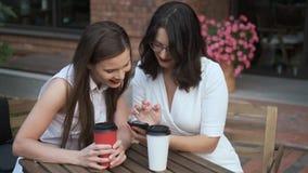 Η νέα γυναίκα παρουσιάζει στο φίλο της κάτι στο τηλέφωνό της δύο επιχειρηματίες κάθονται σε έναν πίνακα σε έναν θερινό καφέ και απόθεμα βίντεο