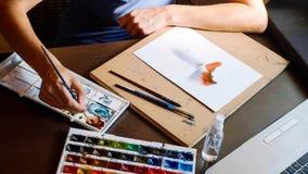 Η νέα γυναίκα περνά ένα μάθημα στο watercolor χρωματίζοντας on-line στο σπίτι στοκ φωτογραφίες με δικαίωμα ελεύθερης χρήσης
