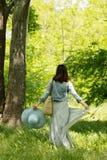 Η νέα γυναίκα περπατά σε ένα πάρκο στο καπέλο και μια μακριά φούστα με το α Στοκ Φωτογραφίες