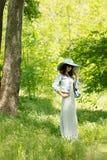 Η νέα γυναίκα περπατά σε ένα πάρκο στο καπέλο και μια μακριά φούστα με το α Στοκ εικόνα με δικαίωμα ελεύθερης χρήσης