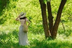Η νέα γυναίκα περπατά σε ένα πάρκο στο καπέλο και μια μακριά φούστα με το α Στοκ φωτογραφία με δικαίωμα ελεύθερης χρήσης