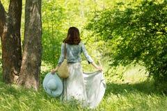 Η νέα γυναίκα περπατά σε ένα πάρκο στο καπέλο και μια μακριά φούστα με το α Στοκ Εικόνες
