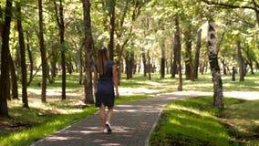 Η νέα γυναίκα περπατά στο πάρκο Το κορίτσι στην καλή διάθεση χαμογελά το περπάτημα στο πάρκο πόλεων Πηγαίνει σε μια πορεία α πίσω απόθεμα βίντεο