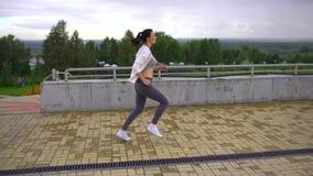 Η νέα γυναίκα πηγαίνει μέσα για τον αθλητισμό, τρέχει στον τρόπο να σταθμεύσει 4 Κ απόθεμα βίντεο