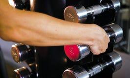 Η νέα γυναίκα πλησιάζει έναν αλτήρα και τους παίρνει στη γυμναστική για την άσκηση workout στοκ εικόνα