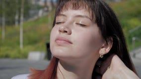 Η νέα γυναίκα πορτρέτου που κλείνει τα μάτια της που απολαμβάνουν τις ακτίνες ήλιων παίρνει ένα Sunbath απόθεμα βίντεο