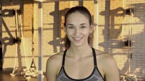 Η νέα γυναίκα πορτρέτου που χαμογελά κατά τη διάρκεια του σπασίματος στην κατάρτιση ικανότητας στη γυμναστική απόθεμα βίντεο