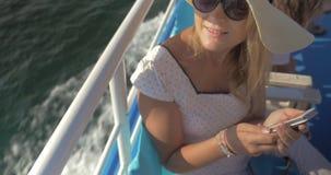Η νέα γυναίκα που ασχολείται με το smartphone είναι στο σκάφος και τη τοπ άποψη χαμόγελου φιλμ μικρού μήκους