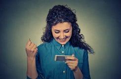 Η νέα γυναίκα που εξετάζει το κινητό τηλέφωνο και την αντλώντας πυγμή χαμόγελού της γιορτάζει την επιτυχία Στοκ εικόνα με δικαίωμα ελεύθερης χρήσης