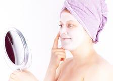 Η νέα γυναίκα που εφαρμόζει την του προσώπου μάσκα κοιτάζει Στοκ Εικόνες