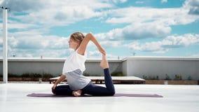 Η νέα γυναίκα που κάνει την άσκηση ένα γιόγκας με πόδια περιστέρι βασιλιάδων θέτει σε σε αργή κίνηση φιλμ μικρού μήκους