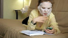 Η νέα γυναίκα που κάνει την του προσώπου μάσκα μασκών με να καθαρίσει τη μάσκα, χτυπά στον καναπέ με το smartphone στο σπίτι στοκ φωτογραφίες με δικαίωμα ελεύθερης χρήσης
