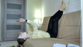 Η νέα γυναίκα που κάνει την του προσώπου μάσκα μασκών με να καθαρίσει τη μάσκα, χτυπά στον καναπέ με το smartphone στο σπίτι στοκ φωτογραφίες