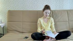 Η νέα γυναίκα που κάνει την του προσώπου μάσκα μασκών με να καθαρίσει τη μάσκα, χτυπά στον καναπέ με το smartphone στο σπίτι στοκ εικόνες